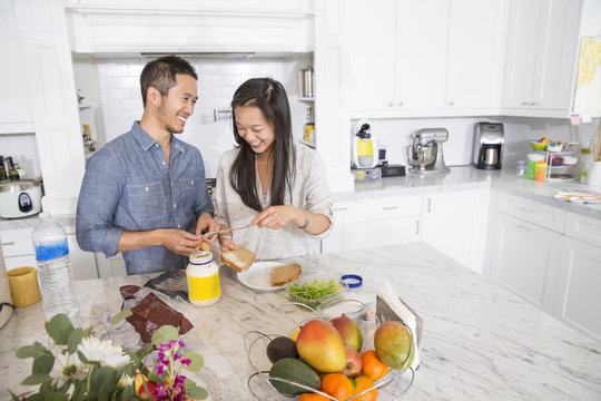 Mid adult couple preparing sandwich in kitchen