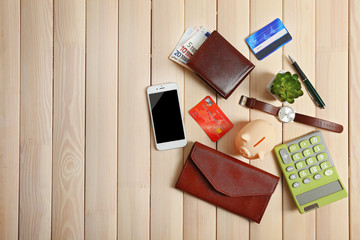 Piggy bank with mobile phone, wallet and other accessories on wooden table, top view