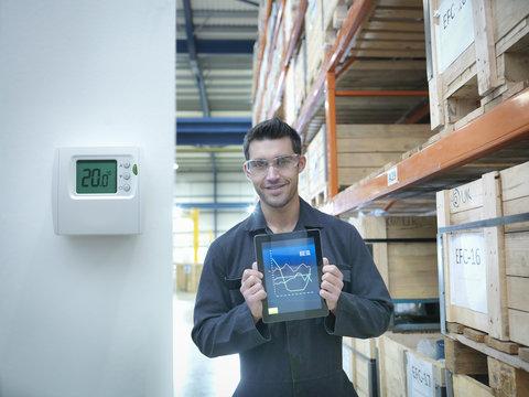 Proud factory worker showing energy saving on digital tablet in factory, portrait