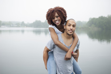 Portrait of young man giving woman piggyback