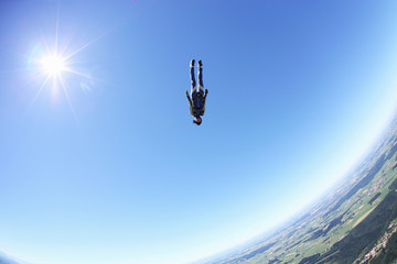 Female skydiver free falling head first above Leutkirch, Bavaria, Germany