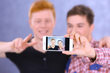 Two teenager boys making photo by their self with mobile phone on grey background, close up