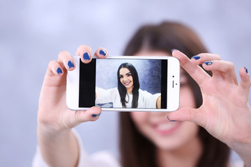 Young attractive girl making photo by her self with mobile phone on grey background, close up