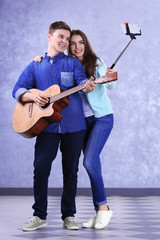 Teenager couple with guitar using stick for photo by their self on grey background