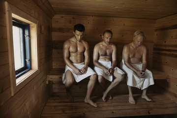 Three men sitting in sauna with heads bowed