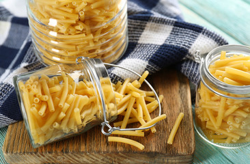 Raw pasta in glass jars on wooden table closeup