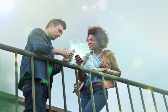 Young couple using smartphones with glowing lights coming out of them