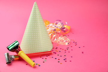 Dotted Birthday hat with serpentine streamer and noise makers on pink background