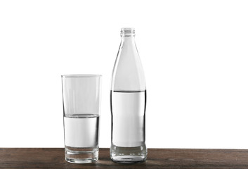 Bottled water with a glass on the grey background, close up