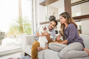 Couple petting cute dog on sitting room sofa