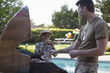 Male soldier and boy barbecuing burgers at homecoming party