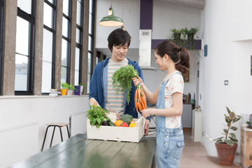 Young couple in kitchen with box of vegetables holding carrots