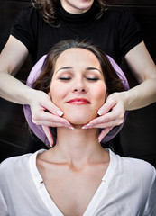 Aesthetician massaging young woman's chin