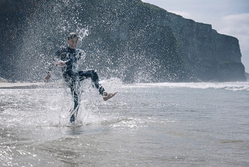 Boy wearing wetsuit, splashing in sea