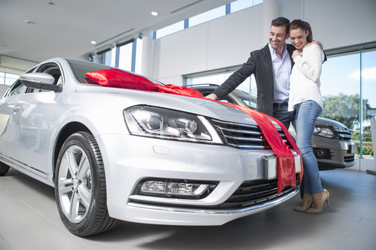 Man looking at new car with red bow with girlfriend in car dealership