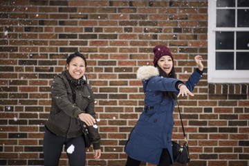 Two you adult females throwing snowballs