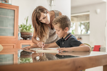 Mother and son looking at homework at dining table