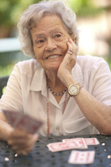 Senior woman playing cards at garden table