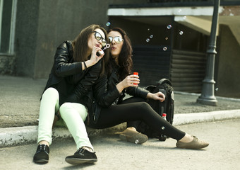 Two young woman blowing bubbles on street