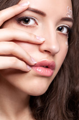 Close-up portrait of young woman with face art  make up and mani