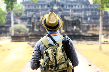 Young traveler wearing a hat with backpack and tripod - at Angkor Wat, Siem Reap, Cambodia