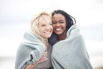 Gay couple wrapped in blanket on beach
