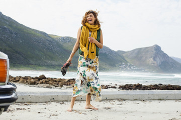 Young woman laughing on beach, Cape Town, Western Cape, South Africa