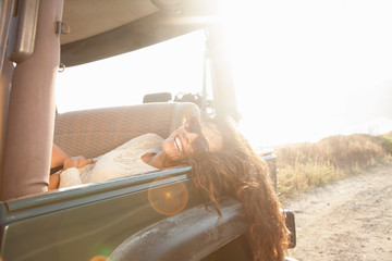 Portrait of young woman reclining in back seat of jeep at coast, Malibu, California, USA