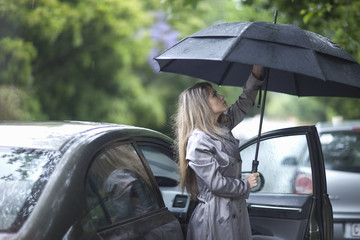 Young woman struggling to put up umbrella