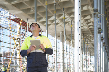 Site manager using digital tablet on construction site