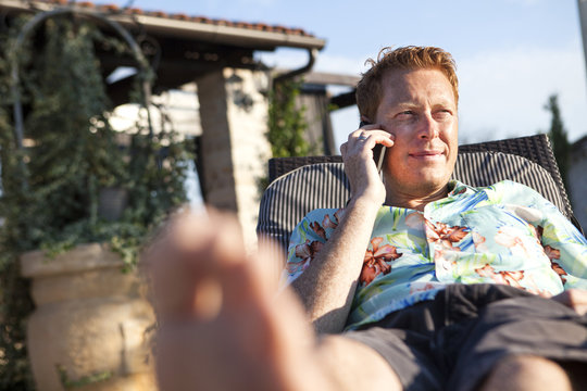 Mid adult man lying on sun lounger on phonecall