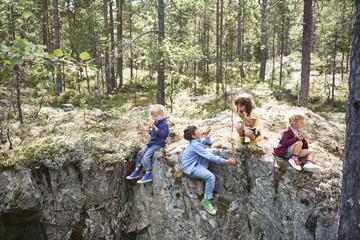 Children sitting on rocks in forest eating picnic