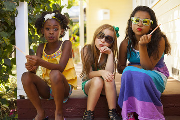 Three girls pulling faces on porch