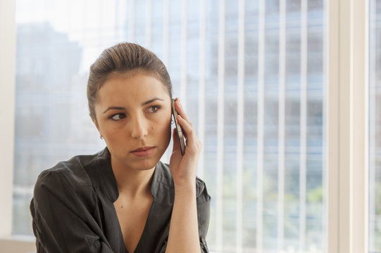 Unhappy businesswoman using cellphone in office
