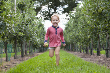 Boy running through apple orchard