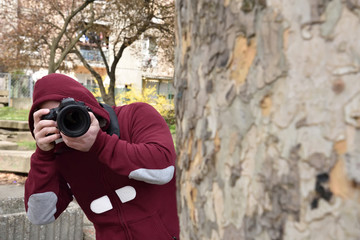 Mysterious paparazzi photographer with the hood on his head lurking behind the tree