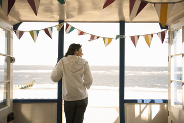 Woman looking out from beach hut, Southwold, Suffolk, UK