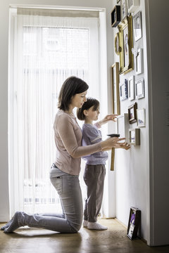 Mother and daughter hanging picture on wall