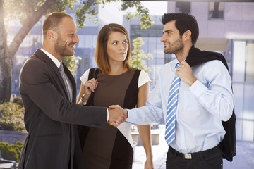 Business associates shaking hands on the street