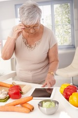 Old lady using tablet in kitchen