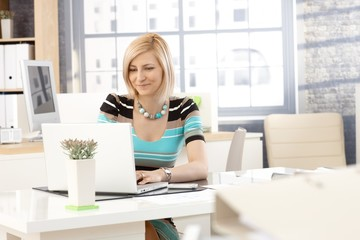 Casual secretary working with laptop computer