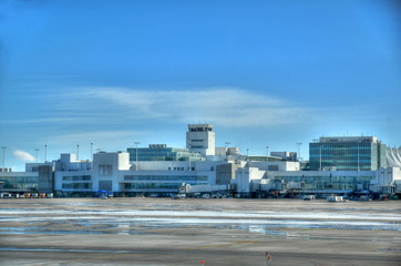 Typical view of international airport outdoors with an air traffic control tower  on a clear blue sky