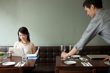Young woman with digital tablet in restaurant, waiter setting table