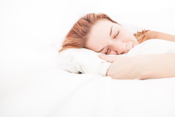 Young woman sleeping with a smile in her bed