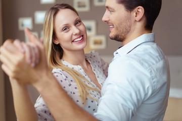 lachende frau tanzt mit ihrem freund durch die wohnung