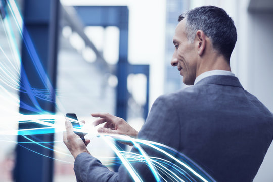 Waves of blue light and businessman using touchscreen on smartphone