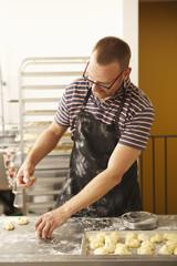 Male baker shaping dough in bakery