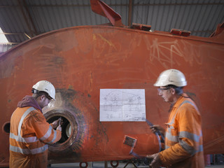 Engineers working on excavator parts in surface coal mine