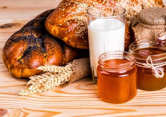 tasty buns with poppy and sesame milk and honey on wooden backgr