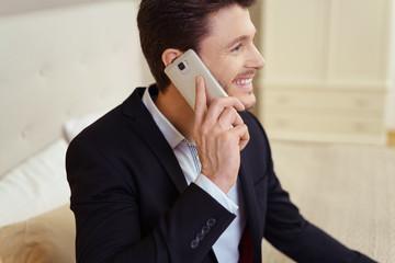 zufriedener geschäftsmann sitzt im hotelzimmer und telefoniert mit seinem smartphone